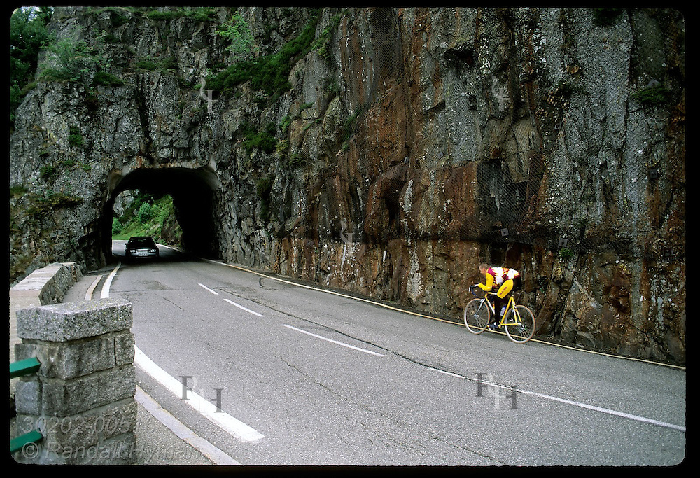 Cyclist pedals toward rock tunnel on road to Col de la Schlucht pass in the Vosges Mtns; Alsace. France