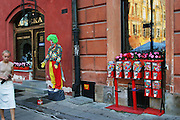 Clown mime, young woman and gumball machines in Warsaw Poland, Old Town Square area, on summer evening.