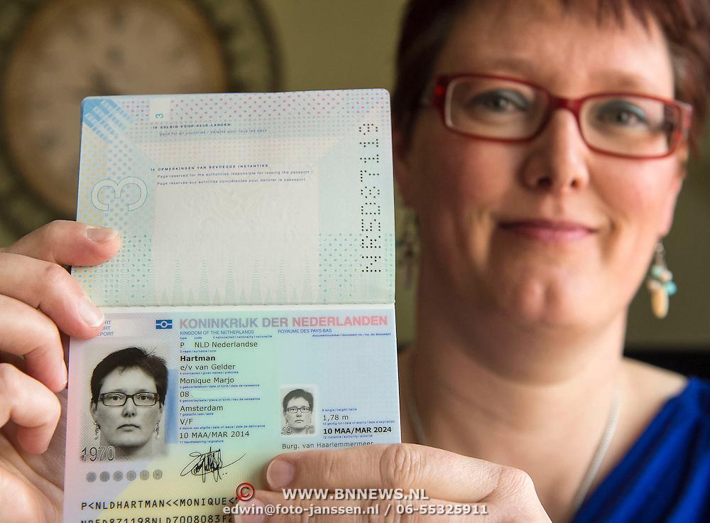 Hoofddorp 12-03-2014. In het bijzijn van de burgemeester van Haarlemmermeer, Theo Weterings, reikte minister Plasterk van Binnenlandse Zaken en Koninkrijksrelaties vanmorgen het nieuwe paspoort uit aan inwoner van Hoofddorp, mevrouw Van Gelder-Hartman. Dit nieuwe paspoort is, net als de nieuwe identiteitsbewijzen, tien jaar geldig in plaats van vijf jaar. Op de foto: vol trots toont mevrouw Van Gelder-Hartman het nieuwe paspoort.
