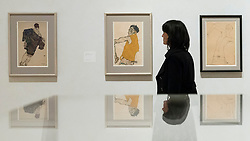 """© Licensed to London News Pictures. 31/10/2018. LONDON, UK. A staff member views (L to R) """"Redemption"""", 1913, """"Self-portrait in Yellow Waistcoat"""", 1914, and """"Self-portrait"""", 1914, all by Egon Schiele. Preview of """"Klimt / Schiele:  Drawings from the Albertina Museum,Vienna"""" exhibition at the Royal Academy.  Over 100 works on paper are on display in an exhibition which marks the centenary of the deaths of the two most celebrated and pioneering figures of early twentieth-century art.  The show runs 4 November to 3 February 2019.  Photo credit: Stephen Chung/LNP"""