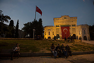 At dusk, men socialize in Beyazit Square outside the entrance to Istanbul University.