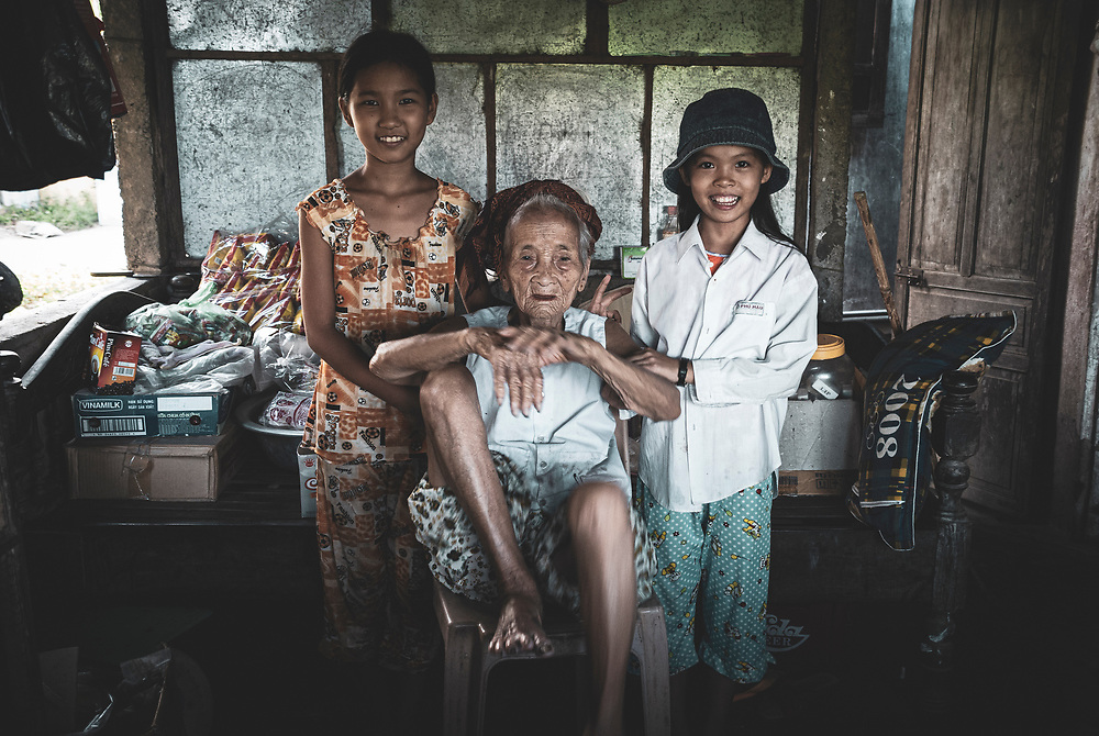 Hue, Vietnam - July 17, 2007: An old woman and children in a home in a village near Hue, Vietnam.