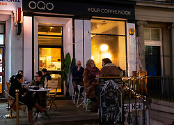 Night view of people sitting outside small  OQO cafe on Leith Walk, Edinburgh, Scotland, UK