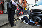 Police observe two of four activists who locked themselves below a van in St Martins Lane near Covent Garden in central London on Monday, Aug 23, 2021. This is a two week planned of action against new fossil fuel investments. XR protestors are aiming to occupy parts of central London for two weeks from Monday, aiming to force the Government to halt all new investment in fossil fuels. (VX Photo/ Vudi Xhymshiti)