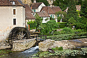 Traditional French houses, water wheel and millrace at Angles Sur L'Anglin medieval village, Vienne, near Poitiers, France