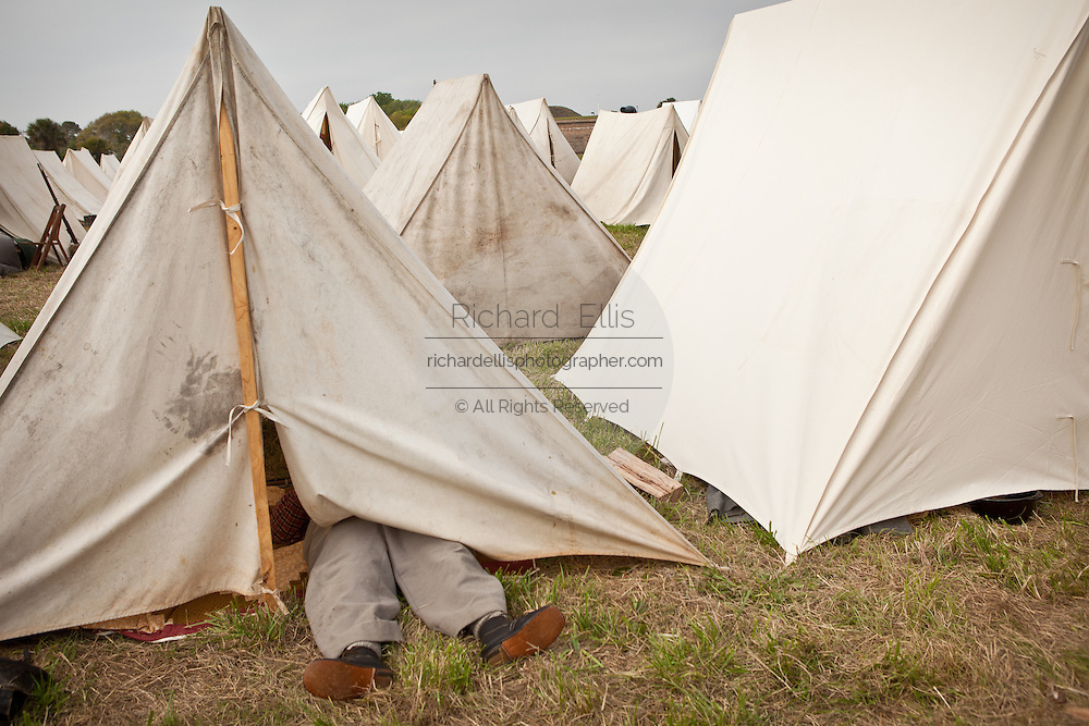 Confederate re-enactor sleeping with his feet out of his tent during the 150th commemoration of the US Civil War Charleston, SC.