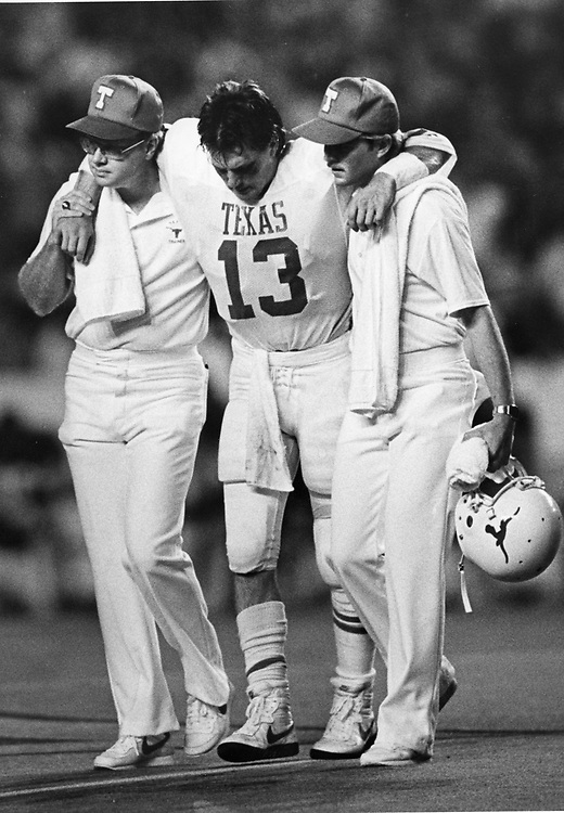 ©1986 Injured Texas football player leaves the field of play with the help of trainers