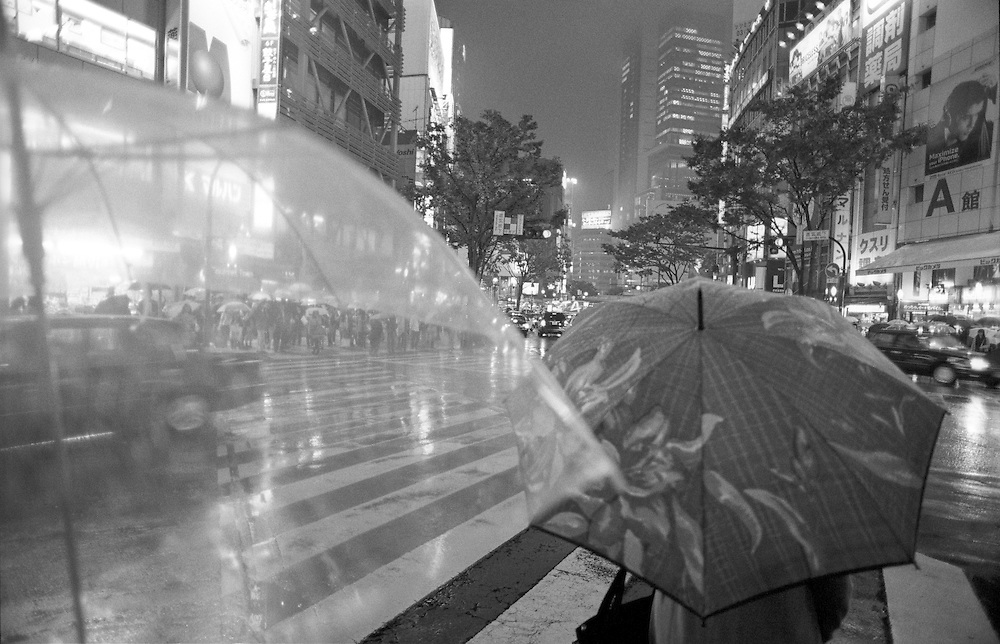 Shoppers, workers and business people wait in the rain with their umbrellas to cross a busy road in Shibuya, one of Tokyo's busiest neighbourhoods.