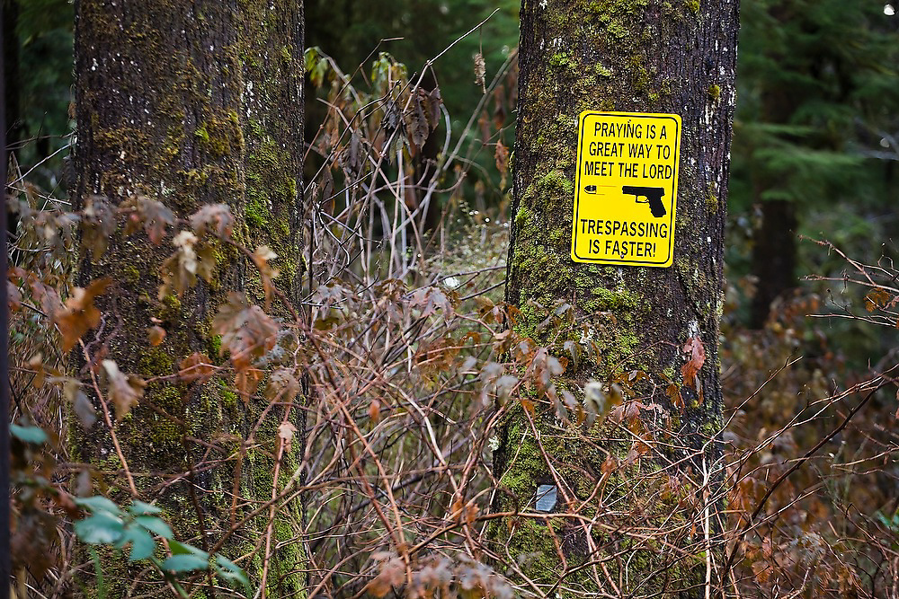 """A sign at the entrance to a private land holding along the north shore of Lake Quinault, on the edge of Olympic National Park, Washington reads """"Praying is a great way to meet the lord, Trespassing is faster."""""""