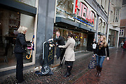 Medewerkers van de Bijenkorf vegen de straten schoon in het centrum van Utrecht. De ondernemers willen dat de stad aantrekkelijk is om te bezoeken, zeker met de stroom bezoekers die met de Giro komen. Door de staking van de vegers is de stad een bende gewordenq