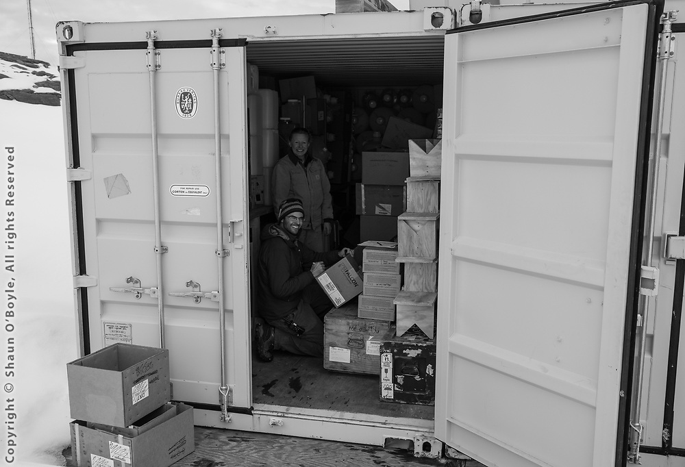Randy Jones and Amy Belcher sorting supplies in the science storage container