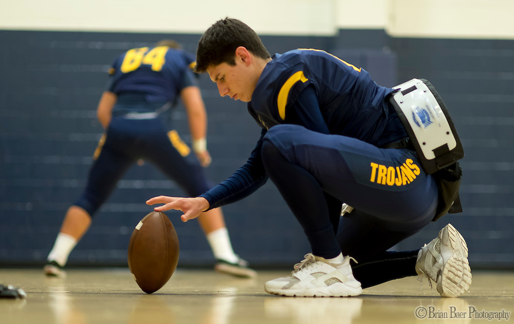 Oak Ridge Trojans Parker Barry (10), practices extra point holds as the Oak Ridge Trojans warm up inside the gym out of the rain before the game as the they host the Granite Bay Grizzlies, Friday Oct 14, 2016.<br /> photo by Brian Baer