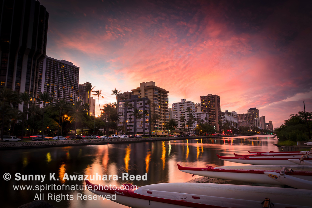 Magenta sunset over Ala Wai Canal and highrise buildings. Outrigger canoes lined up along the shore. Honolulu, Oahu Island, Hawaii.