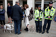 "Two Italian greyhounds at the protest and two police officers. Occupy London protest at St Pauls, October 16th 2011. Protest spreads from the US with this demonstrations in London and other cities worldwide. The 'Occupy' movement is spreading via social media. After four weeks of focus on the Wall Street protest, the campaign against the global banking industry started in the UK this weekend, with the biggest event aiming to ""occupy"" the London Stock Exchange. The protests have been organised on social media pages that between them have picked up more than 15,000 followers. Campaigners gathered outside  at midday before marching the short distance to Paternoster Square, home of the Stock Exchange and other banks.It is one of a series of events planned around the UK as part of a global day of action, with 800-plus protests promised so far worldwide.Paternoster Square is a private development, giving police more powers to not allow protesters or activists inside."