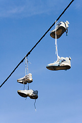 Two pairs of trainers dangling from telephone cable,