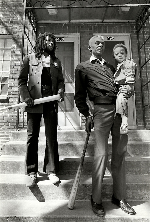 Israel Green leans on a baseball bat as he holds his grandson, two year old Taveris Green, Green and neighbor Chimurenga Jenga keep watch over their neighborhood at Atlanta's Techwood Homes public housing project. Armed with the bats, the two men hoped to keep the killer or killers of Atlanta's childern from their turf.