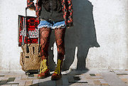 The legs of a female cos-player or costume play girl stand with a wheely bag on the Meiji Jingu bridge in Harajuku. Most weekends cosplayers from all over Tokyo and surrounding areas, and an increasing number of vistors from abroad, gather on this bridge near the revered  Meiji shrine to pose in outlandish costumes that copy styles from popular animation and alternative cultures. Harajuku, Tokyo, May 2005