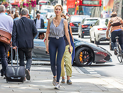 © Licensed to London News Pictures. 22/07/2020. London, UK. A shopper enjoys the warm sunshine on the King's Road in Chelsea as weather forecasters predict 26c today as Londoners get ready for Friday when masks become compulsory in shops in England. Photo credit: Alex Lentati/LNP