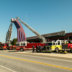 Peach Bottom, PA, USA - October 30, 2014: Two fire trucks, with a giant American flag hanging between their extended ladders, honor a fellow fallen firefighter.