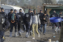 October 27, 2016 - Calais, Nord-Pas-de-Calais-Picardie, France - Refugees pass through the police line to leave the Jungle. The 4th day of the eviction of the jungle in Calais saw the continue demolition of the huts in the Jungle, as well as the first arrests of people who didn'Äôt leave and some minor clashes with activists opposed to the eviction. (Credit Image: © Michael Debets/Pacific Press via ZUMA Wire)