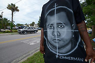 A man who identified himself as Ike wears a shirt portraying George Zimmerman in cross-hairs across the street from the Trayvon Martin memorial in the historically-black Goldsboro neighborhood in Sanford, Fla., Friday, July 12, 2013.  Zimmerman has been charged with second-degree murder for the 2012 shooting death of Trayvon Martin.(AP Photo/Phelan M. Ebenhack)