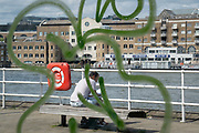 Surrounded by the swirl of sprayed graffiti, a man sits reading on a bench overlooking the Thames river, at Butler's Wharf, on 11th June 2021, in London, England.
