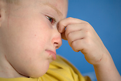 Young boy looking worried; holding his face in his hands,