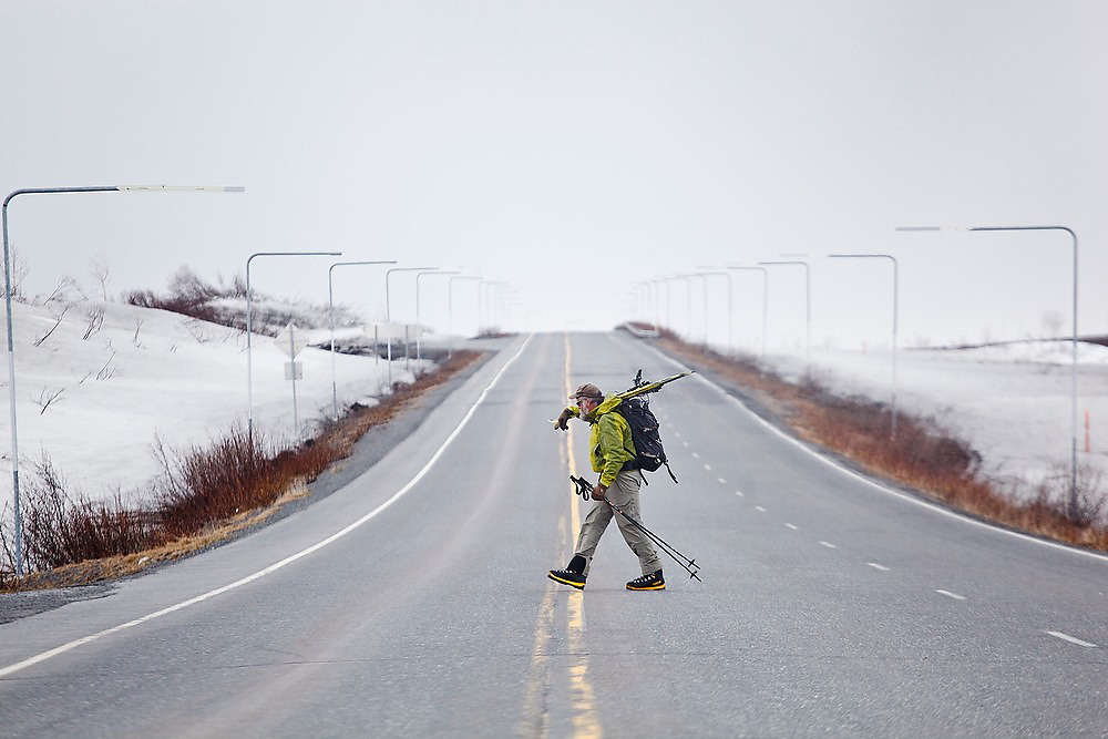 Dr. Tad Pfeffer, a glaciologist with the University of Colorado, walks across the Richardson Highway carrying his skis on his shoulder after backcountry skiing on Thompson Pass, in the Chugach Mountains near Valdez, Alaska.