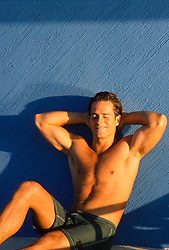 sexy man relaxing against a blue wall