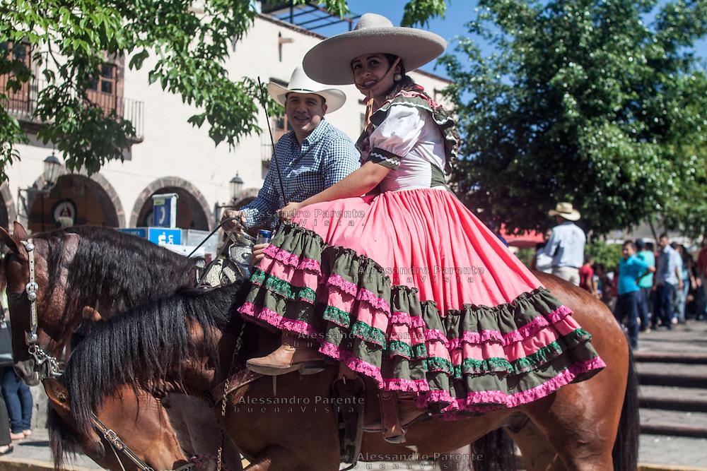 Una bella ragazza e il suo fidanzato festeggiano a cavallo l'indipendenza del Messico nella piazza della città di Tequila, Jalisco, Messico.<br /> A pretty girl and boy in a horse in the mexican indipendence day, Tequila's square. Jalisco, Mexico.