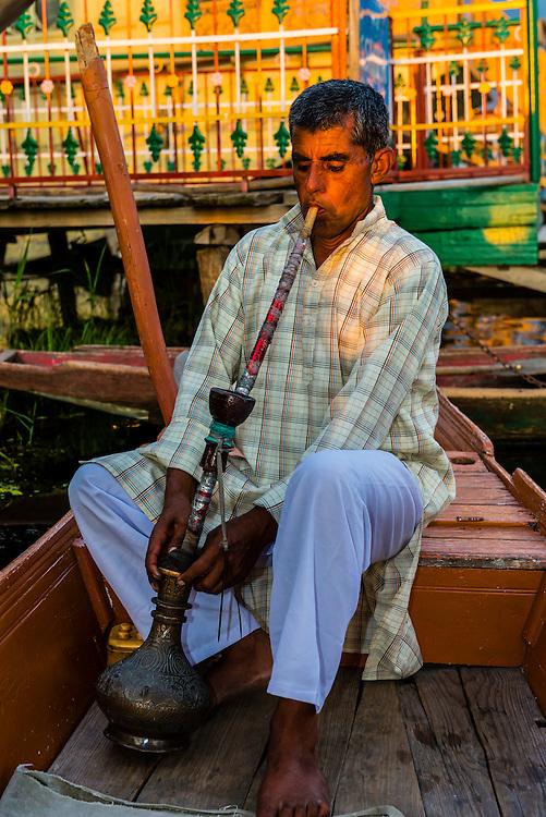 Boatman smoking a waterpipe aboard his shikara (boat) on Dal Lake, Srinagar, Kashmir, Jammu and Kashmir State; India.