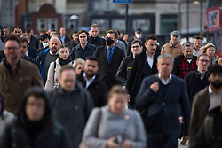 © Licensed to London News Pictures. 21/10/2021. London, UK. Commuters crossing London Bridge this morning. Health Secretary Sajid Javid warned Covid 19 cases could reach 100,000 a day this winter and urged people to take precautions against the virus. Photo credit: Marcin Nowak/LNP