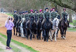 """© Licensed to London News Pictures. 24/02/2021. London, UK. A runner stops to photograph the Household Cavalry Mounted Regiment exercising their horses in the sunshine this morning in Hyde Park, London as weather forecasters predict a warm and sunny week ahead with highs of 17c in London today. This week, Prime Minister Boris Jonson announced his """"Roadmap Map' out of Lockdown with a gradual easing of Covid-19 restrictions with shops, pubs and gyms to open by April, Rule of Six and schools back by March and nightlife back by June. Photo credit: Alex Lentati/LNP"""