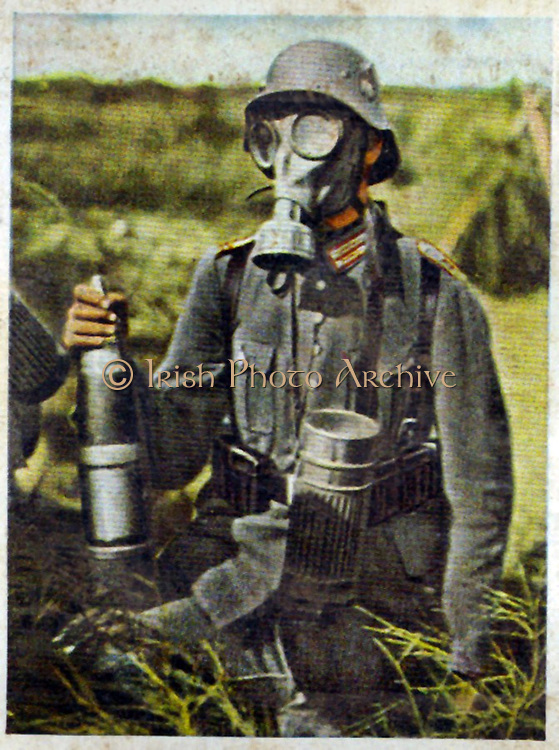German re-armament and militarisation: Chemical warfare preparation. A gunner, holding a shell, on exercises wearing a gasmask. From series of 270 cigarette cards 'Die Deutsche Wehrmacht', Dresden, 1936.