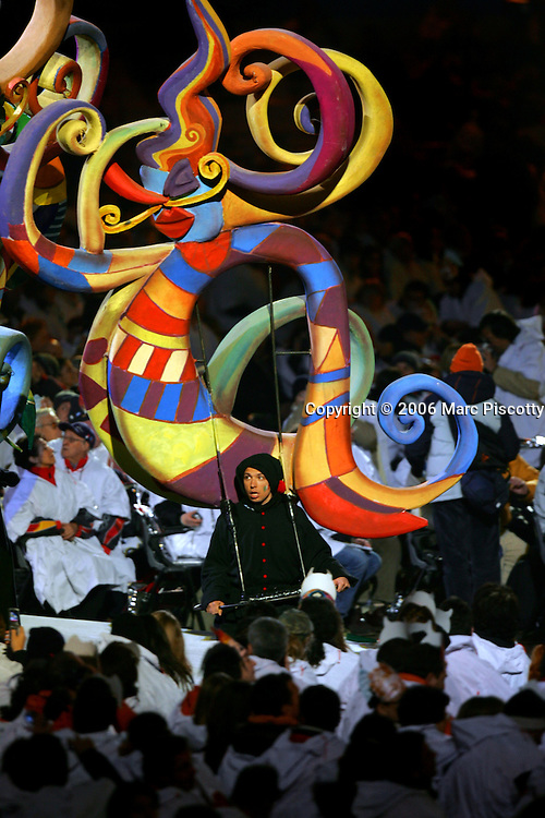 A performer carries a work of art atop his shoulders during the Closing Ceremony for the 2006 Winter Olympics Sunday February 26, 2005 at the Stadio Olimpico in Turin, Italy. The Closing Ceremony featured a dizzying array of circus acts, parades and a general carnival atmosphere. Performers included clowns swivelling in large hoops, ballerinas and tumblers, acrobats dangling high above the stage from ribbons and rings, a stilt walker jumping rope, dancers dressed as Tarot cards and highflying acrobats performing over a tunnel of wind. The Closing Ceremony capped off 16 days of Olympic competition that saw the U.S. win 25 total medals, second to only Germany with 29 total medals..(Photo by Marc Piscotty/ © 2006)