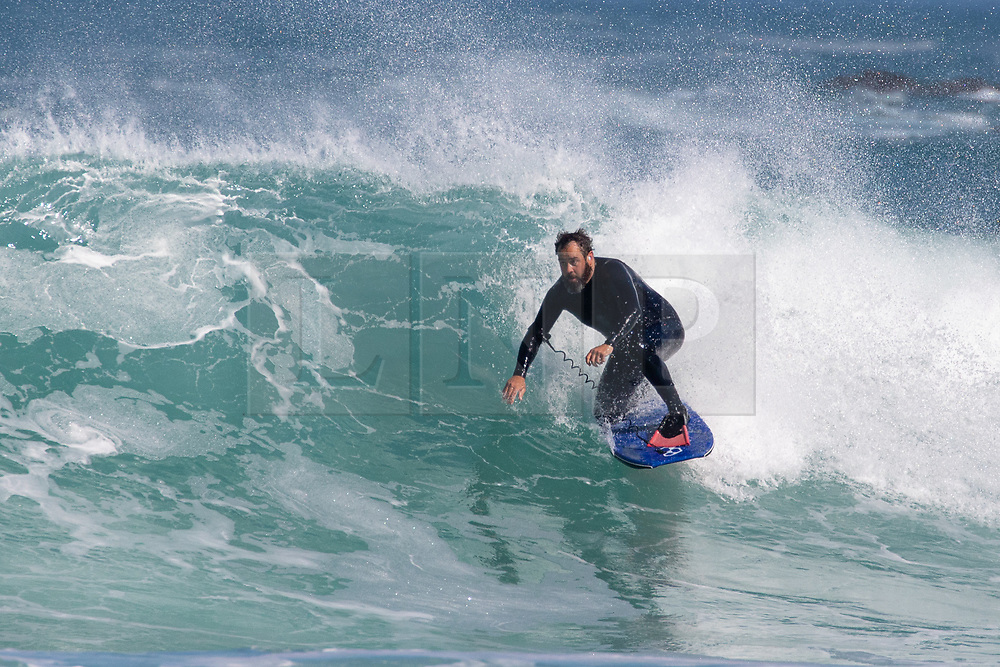 © Licensed to London News Pictures. 25/05/2020. Newquay, UK. A bodyboarder catches a wave near Newquay, Cornwall. There is currently no RNLI Lifeguard service in the county due to Coronavirus (Covid-19). The county has experienced unusual combination of large swell and warm weather during the bank holiday weekend. Photo credit : Tom Nicholson/LNP
