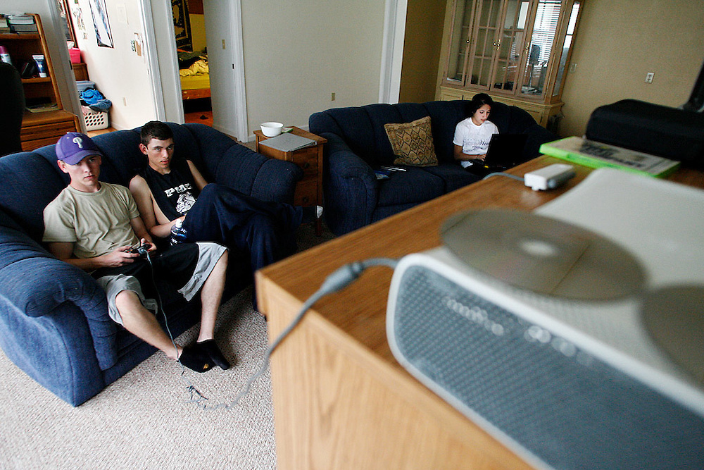 Levi, left, and Luke play Xbox as Silvia Estrada, Levi's fiancee, uses a laptop. The couple both graduated from Pasco High School this year and will attend the University of Idaho.