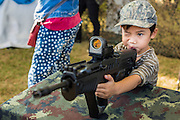 """11 JANUARY 2014 - BANGKOK, THAILAND:  A Thai boy plays with a TAVOR Assault Rifle during Children's Day in Bangkok. The Royal Thai Army hosted a """"Children's Day"""" event at the 2nd Cavalry King's Guard Division base in Bangkok. Children had an opportunity to look at military weapons, climb around on tanks, artillery pieces and helicopters and look at battlefield medical facilities. The Children's Day fair comes amidst political strife and concerns of a possible coup in Thailand. Earlier in the week, the Thai army announced that movements of armored vehicles through Bangkok were not in preparation of a coup, but were moving equipment into position for Children's Day.     PHOTO BY JACK KURTZ"""