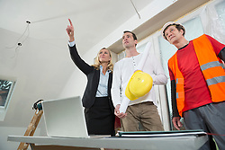 Female architect, construction manager and construction worker at construction site of new building