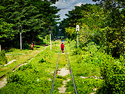 25 NOVEMBER 2017 - YANGON, MYANMAR: Buddhist monks walk on the tracks of the Yangon Circular Train in the countryside outside of Yangon. The Yangon Circular Train is a 45.9-kilometre (28.5 mi) 39-station two track loop system connects satellite towns and suburban areas to downtown. The train was built during the British colonial period, the second track was built in 1954. Trains currently run both directions (clockwise and counter-clockwise) around the city. The trains are the least expensive way to get across Yangon and they are very popular with Yangon's working class. About 100,000 people ride the train every day. A a ticket costs 200 Kyat (about .17¢ US) for the entire 28.5 mile loop.    PHOTO BY JACK KURTZ
