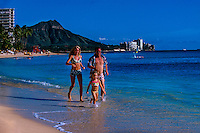 Family jogging down Waikiki Beach, Diamond Head crater in background, Honolulu, Oahu, Hawaii USA