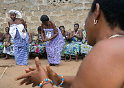 "Benin's Living Dead: The Voodoo Twins Tradition<br /> <br /> 40% of the world's twins are born in Africa. Benin's Fon people have one of the highest occurrences at 1 in 20 births. The high rate of infant mortality and voodoo religion, Benin's national religion, have begot some very particular practices concerning the deaths of one or both of these twins. In many other societies, twins are regarded as bad omens and often killed or abandoned at birth. However, in the Fon culture, twins have always been revered because Nana Buluku, voodoo's androgynous creator of the universe, gave birth to twins. These twins in turn created the voodoo deities that run the world.<br /> <br /> Once a twin dies, a wooden statue called the ""hohovi"" is carved, within which the spirit of the dead child is placed. These figurines are deified and treated almost exactly like the living children. For the Fon, twins are immortal. They continue to live even after their death, bringing blessings or misfortune depending on if there are either pampered or abused.<br /> <br /> Three months after the birth of twins, if they are still living, the parents go collect gifts from other members of their community. If one or both of the twins die, then the mother carries the statues around between her breasts and walks around with a tray on her head, receiving alms for the twins.  All donate some money or food. The mother may even take some wares on display at the market. If a woman is rich or powerful, then she sends someone to conduct this collection in her place. <br /> <br /> In Bopa, a village situated on the banks of Lake Aheme in southern Benin, Dah Tofa and his wife reside. Dah Tofa, an educated man in his 60s, is a voodoo priest. His wife, who is around 40 years old, speaks only Fon. I ask for her name and she tells me the name she was born with, but this causes a bit of an incident. Her husband explains that she was supposed to say ""Hounyoga"", the name of the voodoo goddess she worships whose name she took. Her husband tells me"
