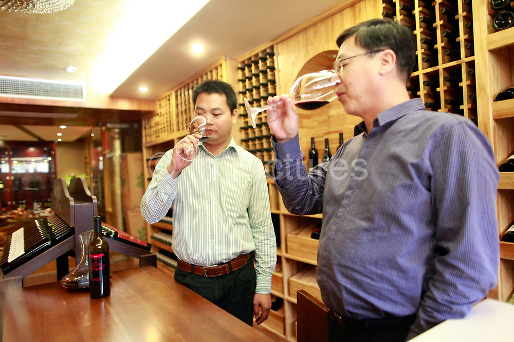 Lin Tiangui, a representative of Winston Wine, shares a glass of wine with Huang Yongqiang, a store manger, at one of its stores in Shanghai, China on 18 October, 2011. Photographer: Qilai Shen/BloombergLin Tiangui, a representative for Australia's Winston Wines Pty, left, and Huang Yongqiang, a store manger for Winston Wines, sample wine at the company's store in Shanghai, China, on Tuesday, Oct. 18, 2011. Australian vineyards, facing slumping exports and rising competition, are turning to China as Chinese buyers creating surging demand among the nation's rich, who are developing a taste for wine and the expression of wealth and class it conveys.