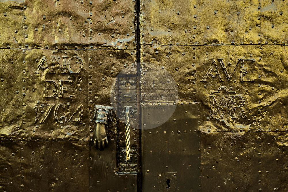 A polished old hammered brass door dated 1764 in the historic center of San Miguel de Allende, Guanajuato, Mexico.