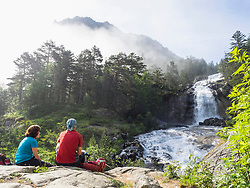 Hikers admiring scenic view of waterfall in Gave De Gaube river, France