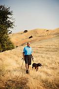 Older man walking dog in field.