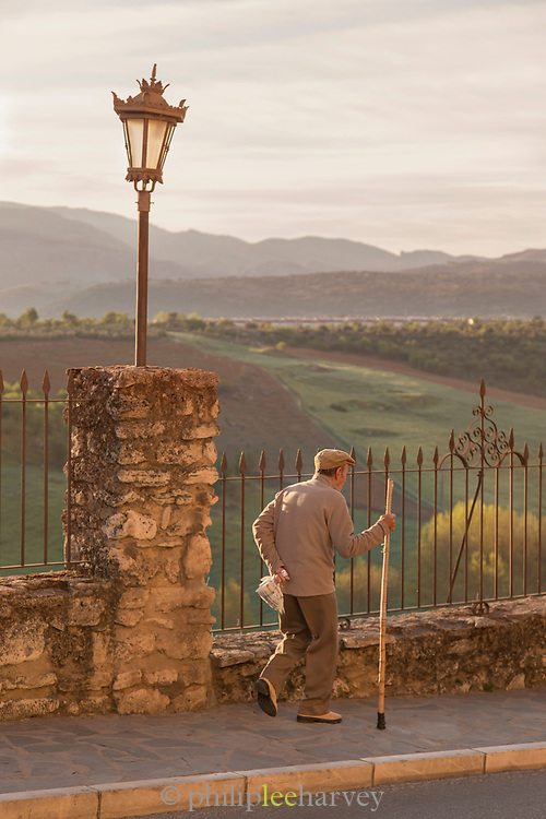 Senior man walking along sidewalk with rolling landscape in background, Ronda, Andalusia, Spain