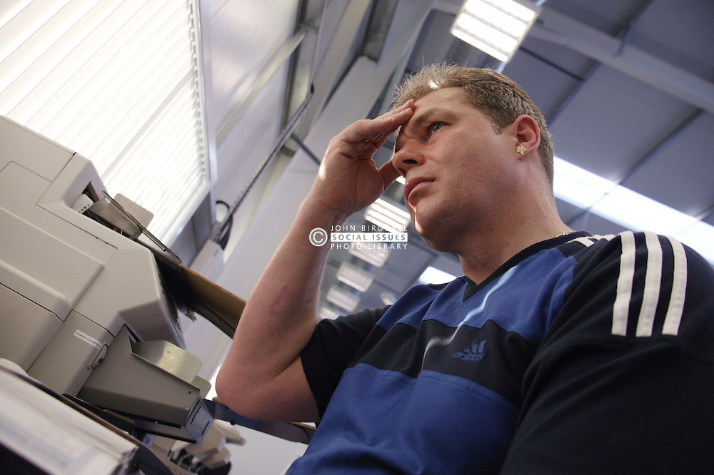Man with epilepsy working as scanning operator in direct marketing office,
