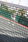 tennis concept Blured figure of a tennis player behind the net