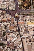 An aerial of a procession leaving a neighborhood church during holy week in Seville, Spain. Street processions are organized in most Spanish towns each evening, from Palm Sunday to Easter Sunday. People carry statues of saints on floats or wooden platforms, and an atmosphere of mourning can seem quite oppressive to onlookers.